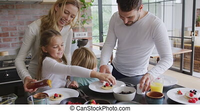 Family garnishing food at dining table in a comfortable home 4k