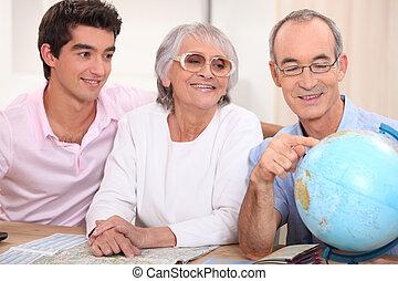 Family gathered around globe and atlas