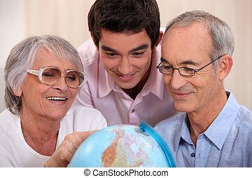 Family gathered around globe