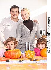 Family gathered around kitchen table preparing pumpkins