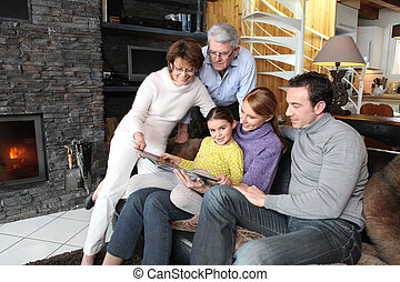 Family gathered together looking at photographs