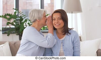 senior mother talking to adult daughter at home - family,...