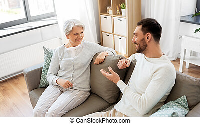 senior mother talking to adult son at home