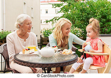 woman with daughter and senior mother at cafe
