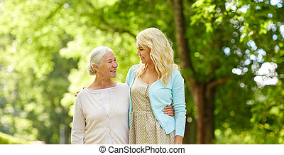 daughter with senior mother hugging at park