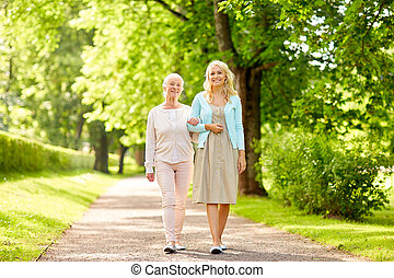 daughter with senior mother walking at summer park
