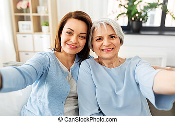senior mother and adult daughter taking selfie
