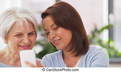 senior mother and adult daughter with smartphone - family,...