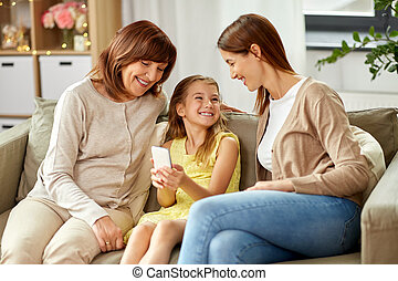 mother, daughter and grandmother with smartphone