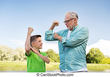 happy grandfather and grandson showing muscles - family, ...