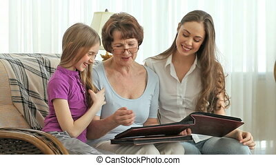 Females of three family generations looking through photo albums