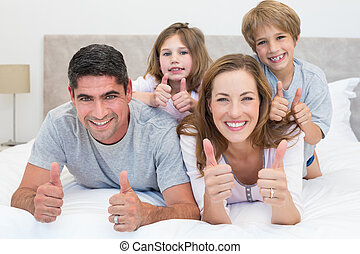 Family gesturing thumbs up in bed