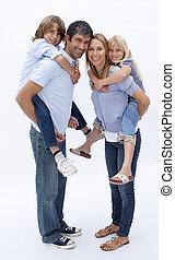 Family giving children piggyback ride against white - Family...