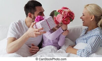 family giving flowers and gift to mother in bed