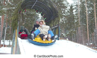 Family glides on an ice slide on a tubing