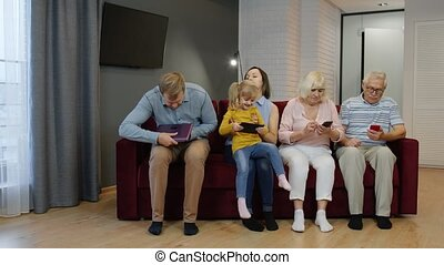 Family goes and sits on the couch with personal gadgets. Spending time at home with mobile phone, tablet, laptop. Addicted to modern technology devices. Social networks, internet obsession concept