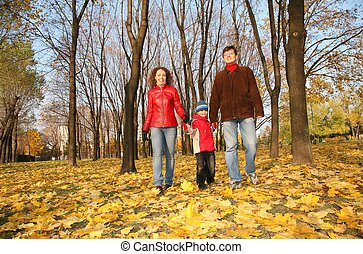 family goes for a walk in the park in autumn
