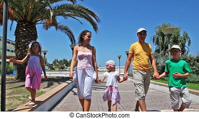 Family goes on walkway lined with palm trees and flowers