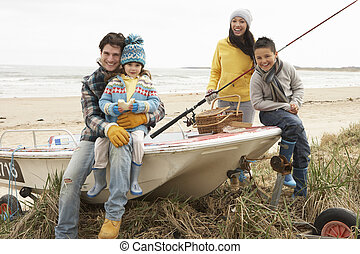 Family Group Sitting On Boat With Fishing Rod On Winter...