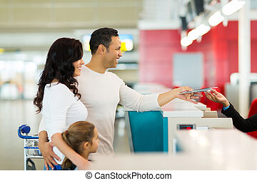 family handing over air ticket at airport at check in...