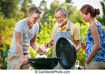 Family having a barbecue party in their garden in summer