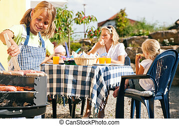 Family having a barbecue party - little kid at the barbecue...