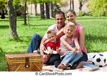 Family having a picnic smiling at the camera