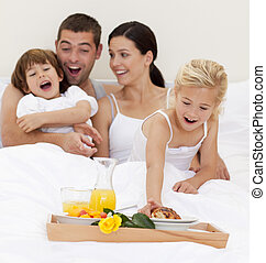 Family having breakfast in bed in the morning