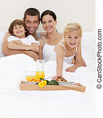 Family having breakfast in bedroom - Smiling family having...