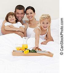 Smiling family having nutritive breakfast in bedroom