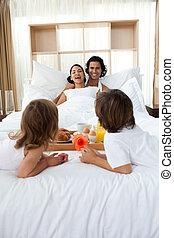 Family having breakfast on the bed