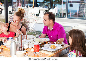 Family having brunch outside on a sunny day