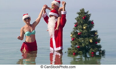 Family having fan at tropical beach posing near Christmas tree in water