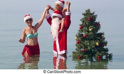 Family having fan at tropical beach posing near Christmas tree in water