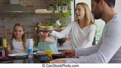 Family having food at dining table in kitchen at comfortable home 4k