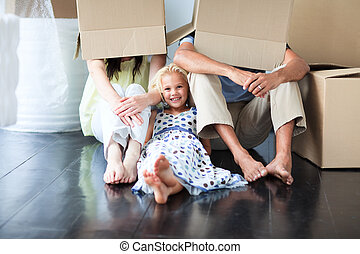 Family having fun after moving house - Young family having...