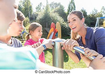 Family having fun at adventure playground in park
