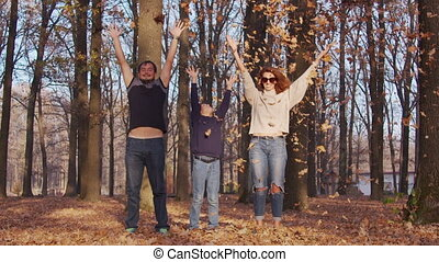 Family having fun in autumn park. Mom father and son throw ...