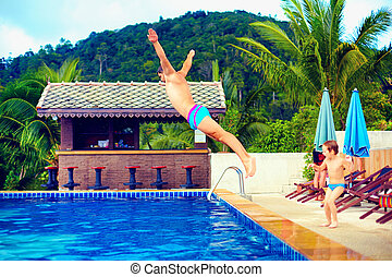 family having fun in pool on tropical vacation