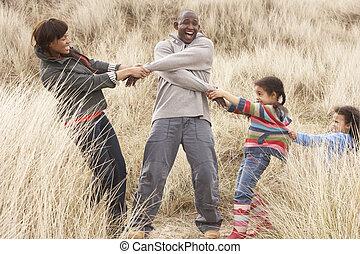 Family Having Fun In Sand Dunes