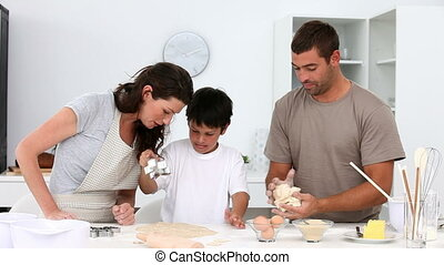 Family having fun in the kitchen while cooking biscuits