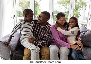 Family having fun on a sofa in living room at home