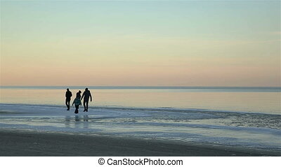 Family having fun on the ice of the Baltic sea