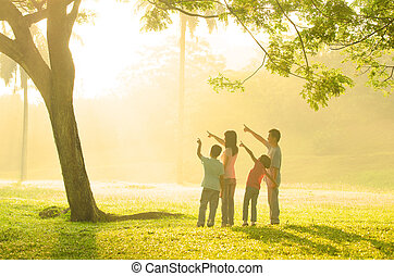 family having fun pointing to somewhere during beautiful sunrise