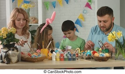 Family having fun while painting and decorating eggs for holiday