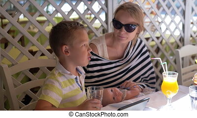 Family having good day. Mother with baby and elder son relaxing in cafe