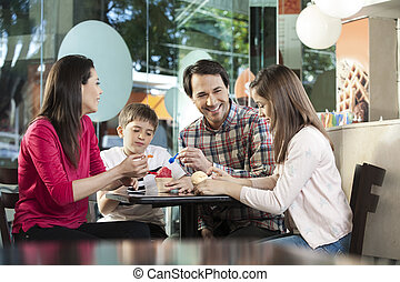 Family Having Ice Creams At Table In Parlor