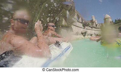 Family having lazy river ride in water park - Mom, dad and...