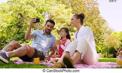 family having picnic and taking selfie at park - family,...