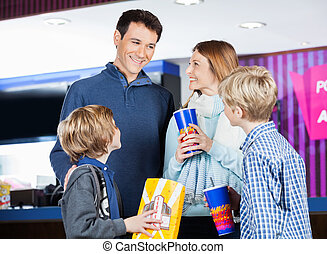 Family Having Snacks By Cinema Concession Stand